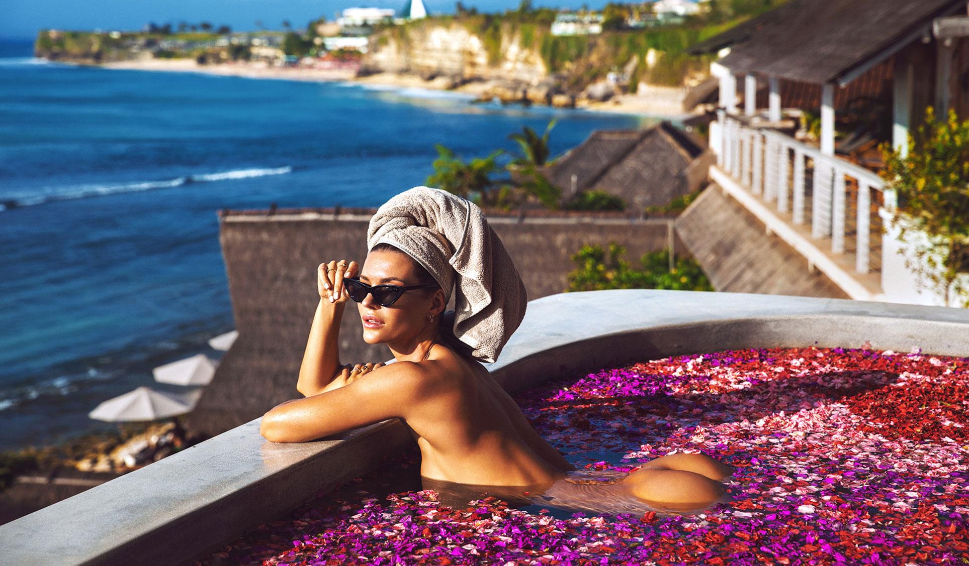 Сексуальная голая девушка в бассейне, заполненном лепестками роз в отеле с шикарным видом на острове Бали / фото 01
