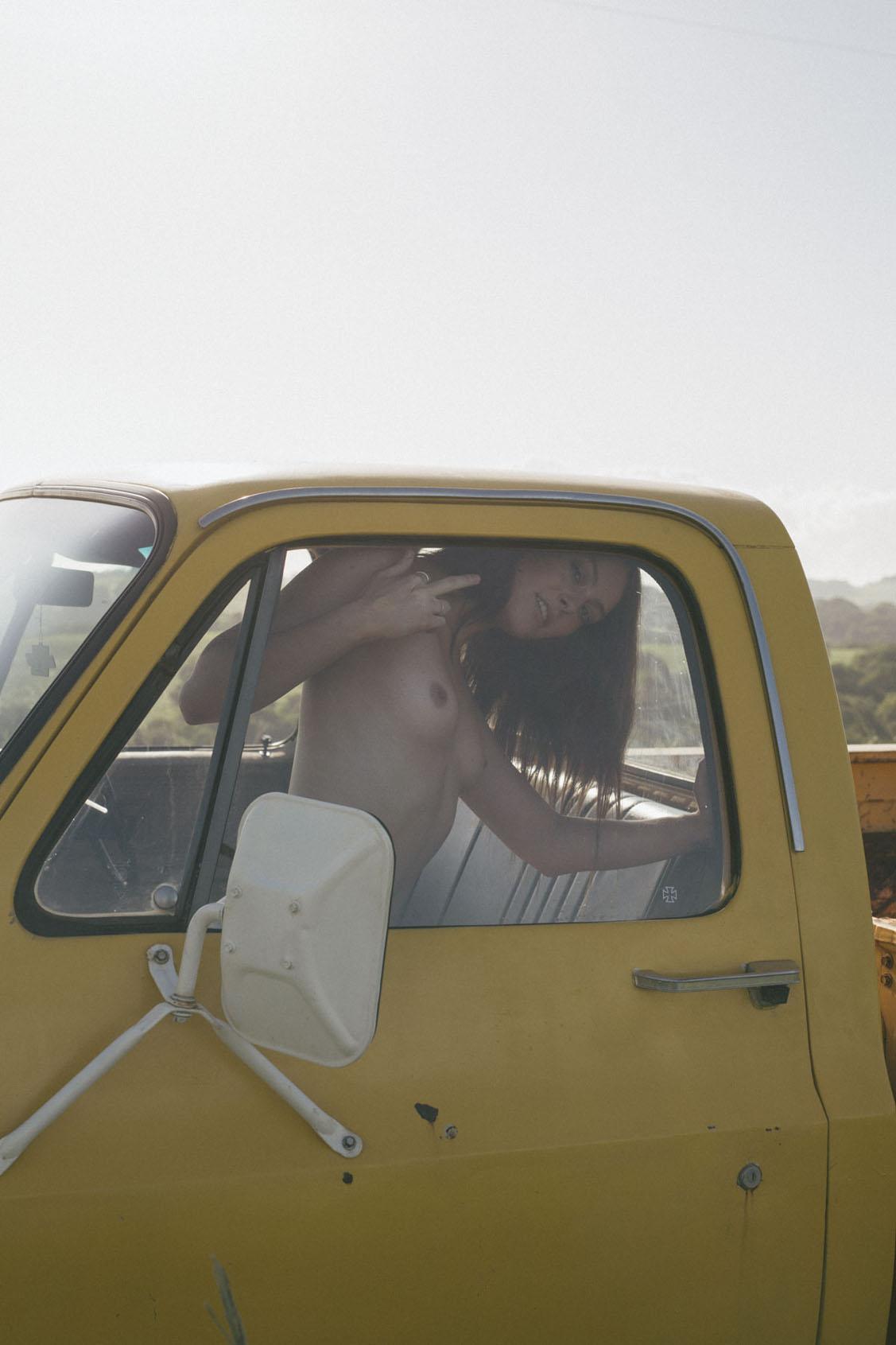 голая девушка в желтом грузовике на пустынной дороге / фото 04