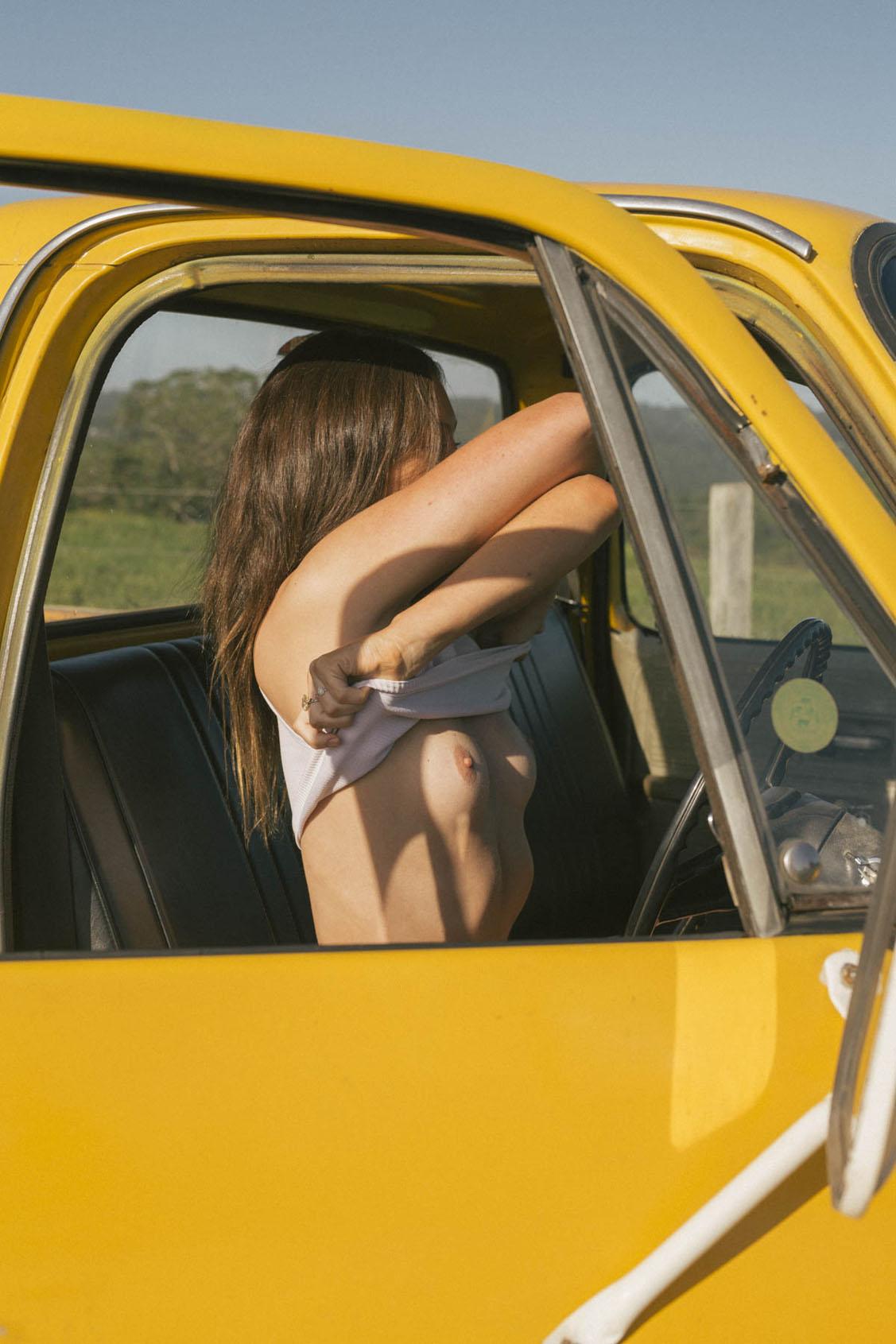 голая девушка в желтом грузовике на пустынной дороге / фото 03