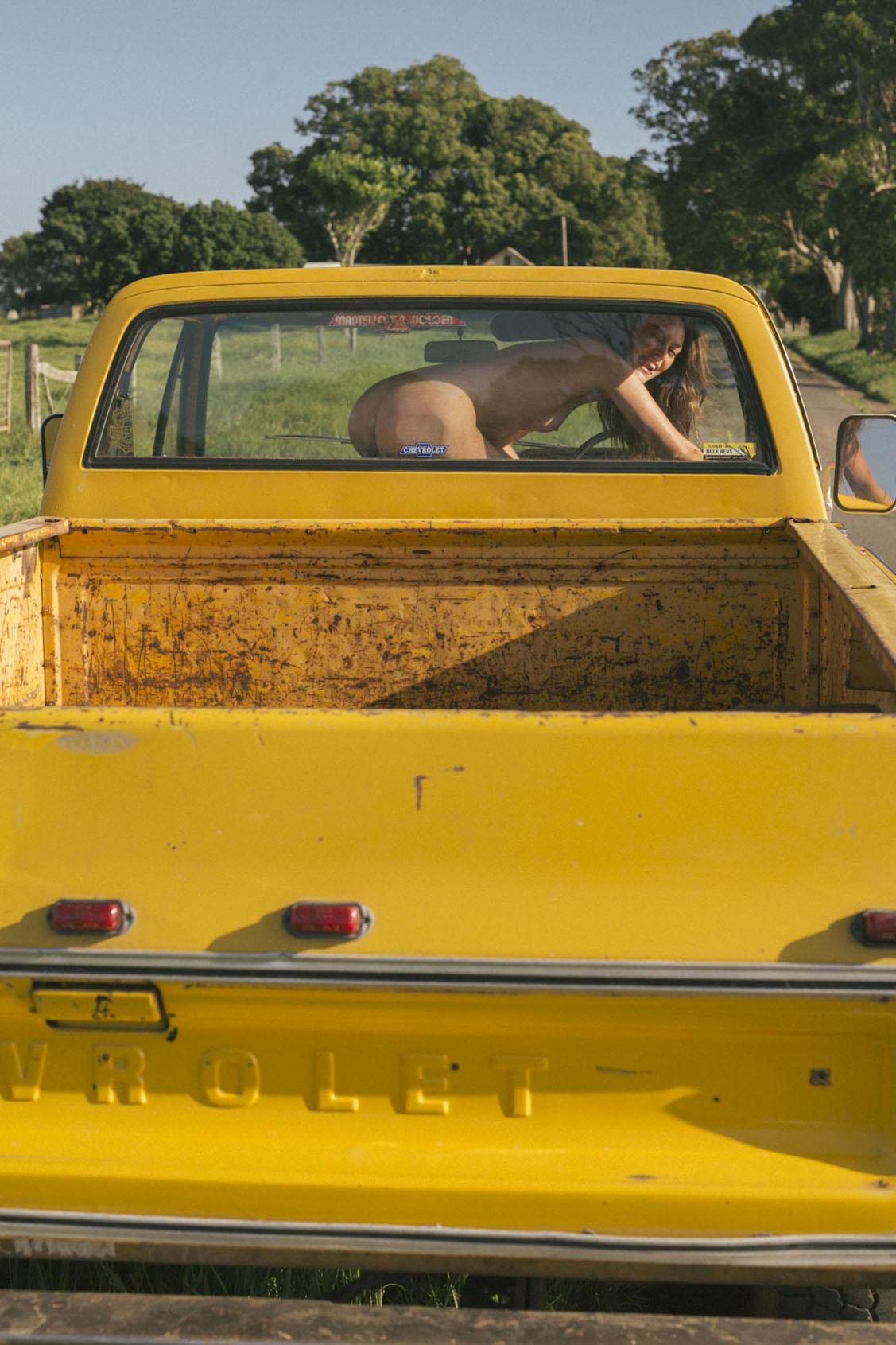 голая девушка в желтом грузовике на пустынной дороге / фото 08