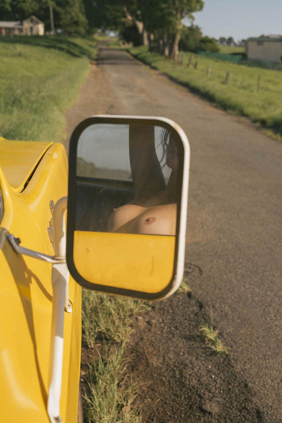 голая девушка в желтом грузовике на пустынной дороге / фото 10