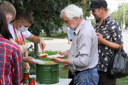 Пожилому мужчине накладывают макароны